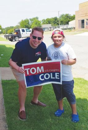 Garrett Calfy (right) and Tom Cole Field Representative Scott Chance (left) assembling campaign signs outside the new Headquarters.